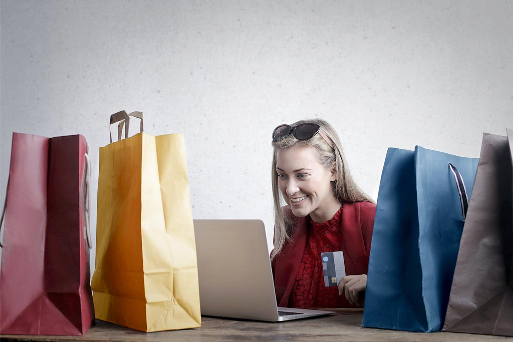 Person Holding. Credit Card with shopping bags all around