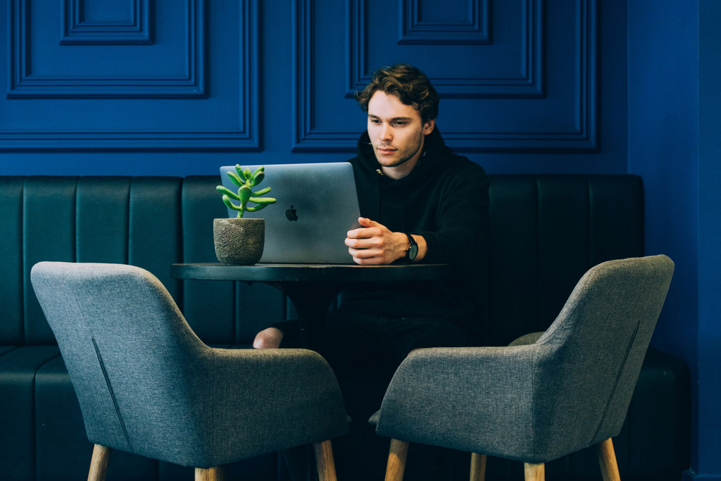 person sitting in a room with a laptop and a blue wall behind him sitting on a blue chair