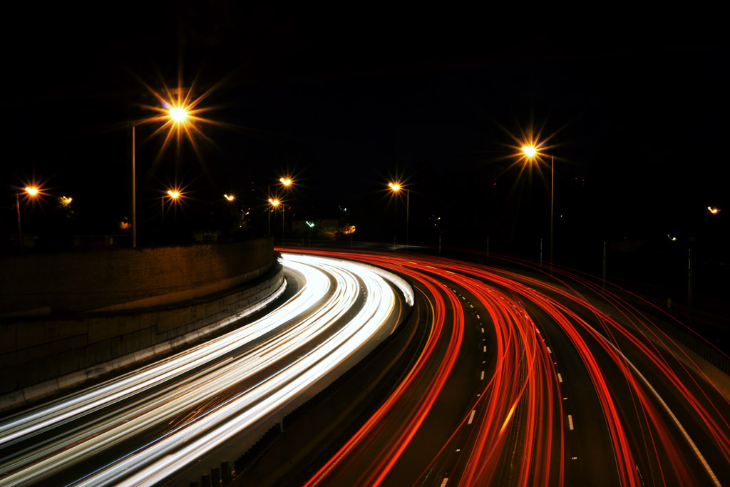 cars driving fast on a road at night