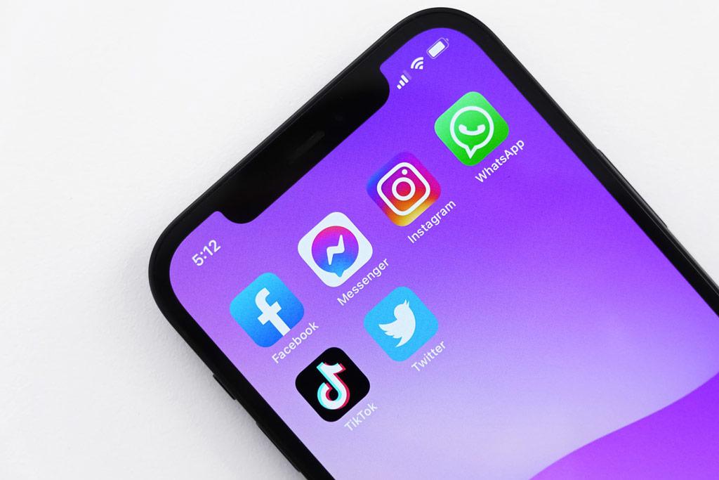 Phone showing app icons of Facebook Messenger Instagram WhatsApp TikTok Twitter