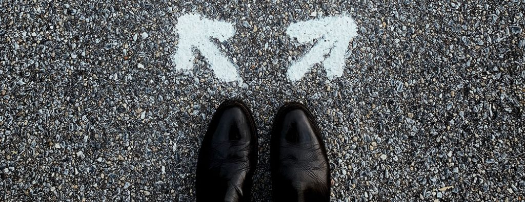 pair of shoes on pavement with two white arrows point in opposite directions