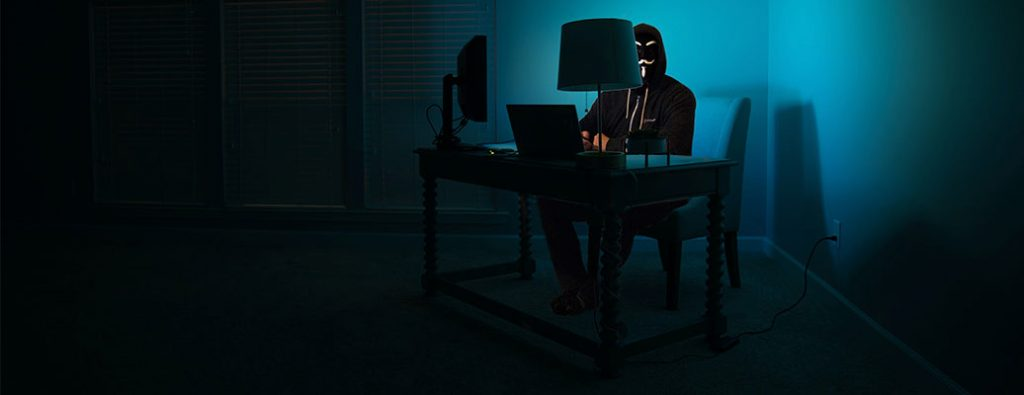 a person hacking on a computer in the dark