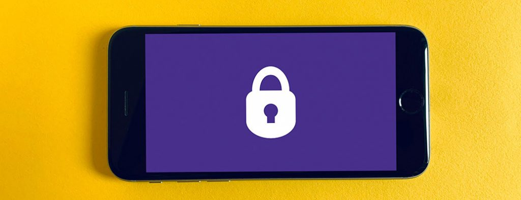 a phone on a yellow background with a lock on the screen